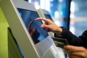 Woman using credit card on automatic ticketing machine